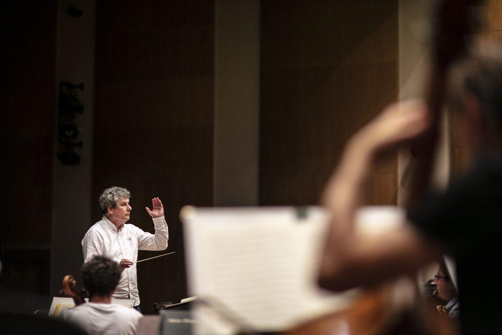 Po lewej stronie dyrygent, w ręku trzyma batutę. Na zdjęciu widać kilku muzyków z instrumentami.