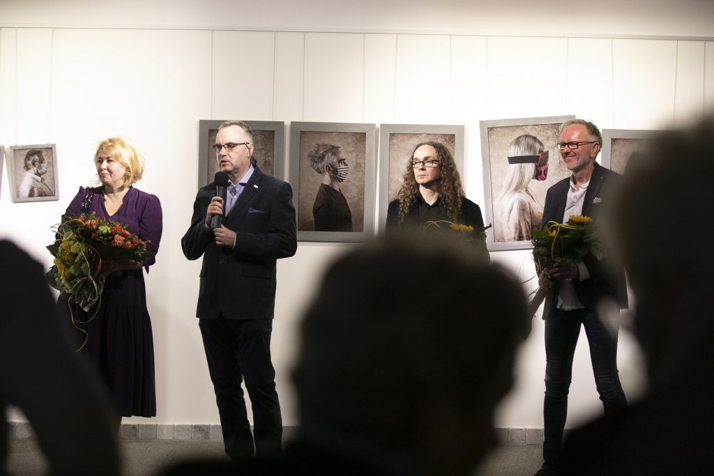 Trzech mężczyzn i jedna kobieta stoją przy ścianie na której wiszą fotografie. Jeden z mężczyzn trzyma mikrofon, reszta osób trzyma bukiety kwiatów.
