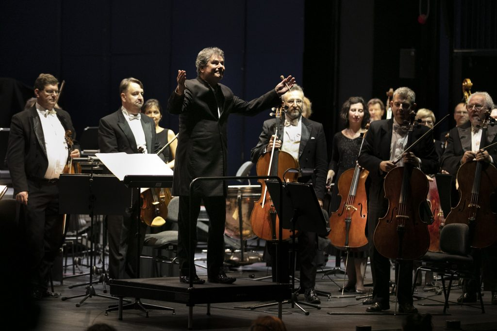 Na podeście stoi dyrygent z rękoma uniesionymi do góry. Wokół niego stoją muzycy z grupy smyczkowej z instrumentami.