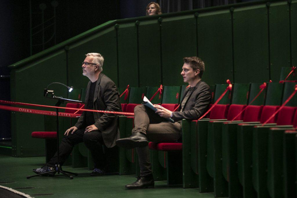 W pierwszym rzędzie na widowni siedzi dwóch mężczyzn. Przed jednym z nich stoi pulpit do nut.