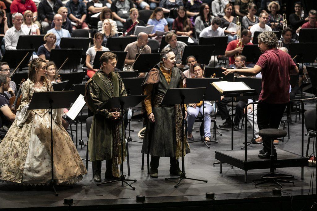 Próba do koncertu. Na scenie przy pulpitach stoją soliści. Patrzą w stronę dyrygenta który stoi po prawej stronie na podeście. Dalej widoczna część orkiestry sekcji smyczkowej i dętej.