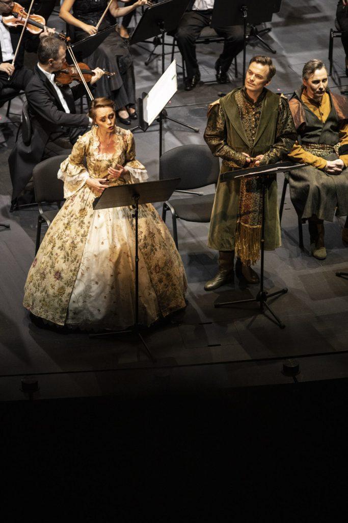 Na scenie stoi solistka w jasnej sukni i dwóch solistów w strojach szlacheckich. Za nimi widocznych kilka osób z sekcji smyczkowej orkiestry.