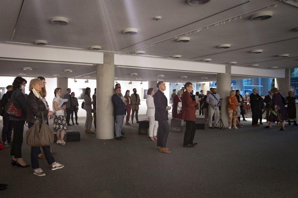 Sala wystawowa. Pomiędzy filarami stoi kilkanaście osób. Wszyscy patrzą w jednym kierunku. Kilka osób trzyma kieliszki.