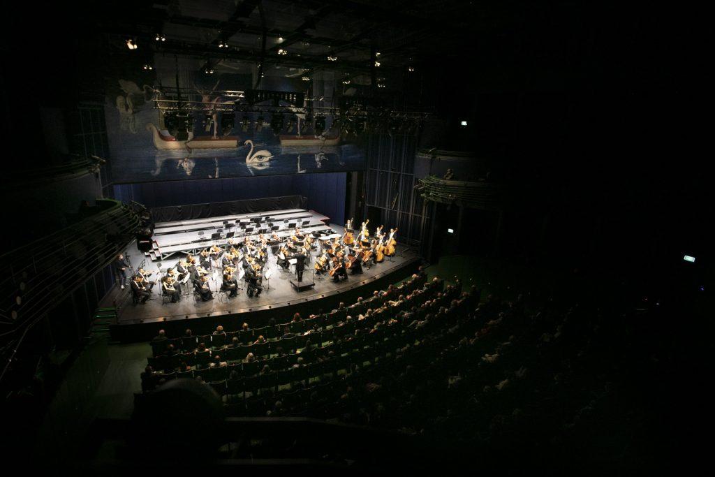 Scena i widownia Opery i Filharmonii Podlaskiej. Widok z balkonu. Na scenie orkiestra z dyrygentem. Widownia wypełniona publicznością na co drugim krześle.