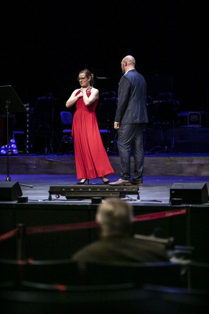 Kobieta w czerwonej sukni trzyma ręce przy szyi. Obok niej stoi mężczyzna w garniturze.