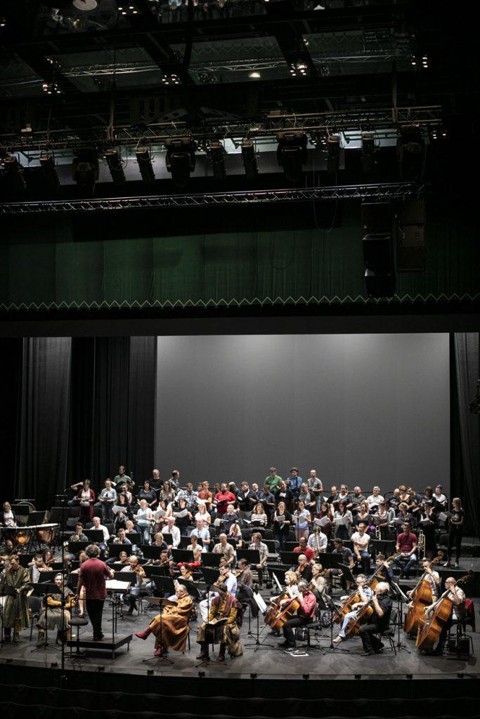 Próba do koncertu. Na scenie soliści, orkiestra i chór. Na środku stoi dyrygent.