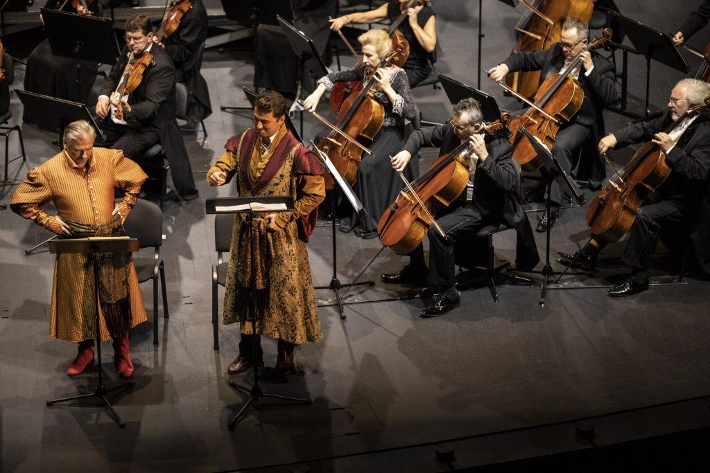 Po lewej stronie stoi dwóch solistów w strojach szlacheckich. Za nimi grupa wiolonczel podczas koncertu.