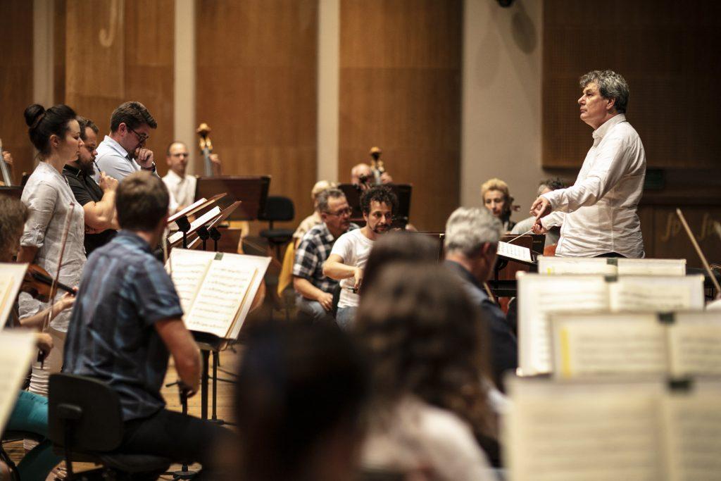 Próba do koncertu. Po prawej stronie stoi dyrygent. Na środku przy pulpitach siedzi kilkanaście osób z instrumentami.