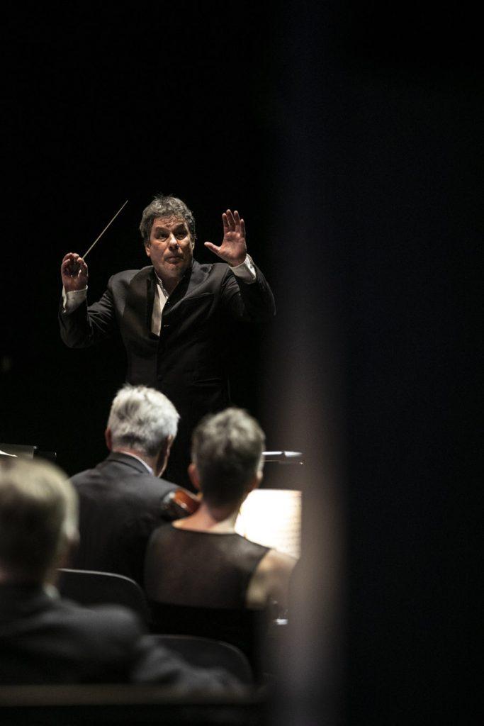Dyrygent trzymający batutę, stoi z uniesionymi rękoma przed pierwszym pulpitem skrzypiec.