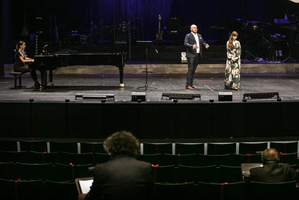 Mężczyzna w garniturze i kobieta w długiej sukience stoją obok siebie. Po lewej stronie stoi fortepian, przy nim siedzi kobieta. Na widowni siedzi dwóch mężczyzn.