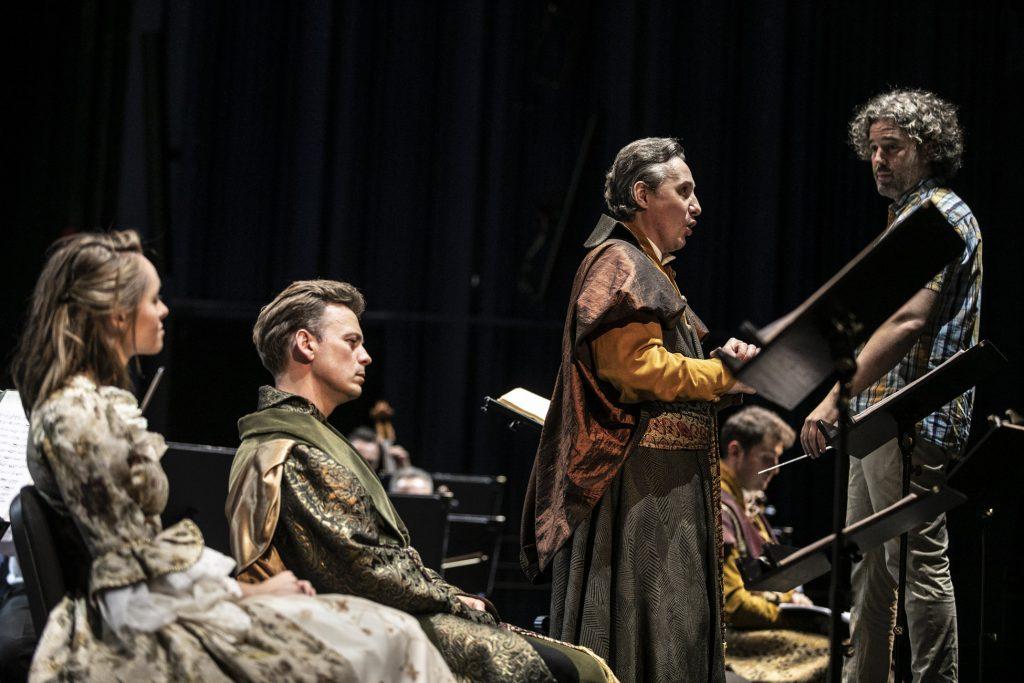 Zdjęcie zrobione z boku. Dwóch solistów, kobieta i mężczyzna siedzą. Jeden stoi przed pulpitem śpiewając. Za nim, na podeście stoi dyrygent.