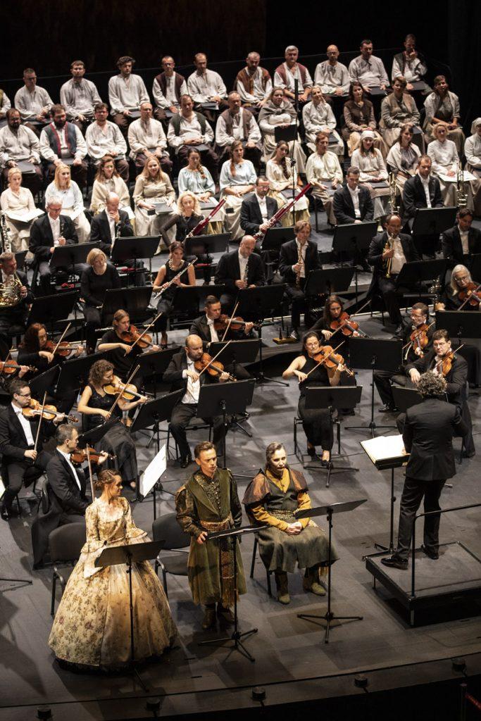 Widok z góry. Od lewej solistka w jasnej sukni i dwóch solistów w kostiumach szlacheckich. Obok dyrygent. Za solistami orkiestra i chór w białych kostiumach.
