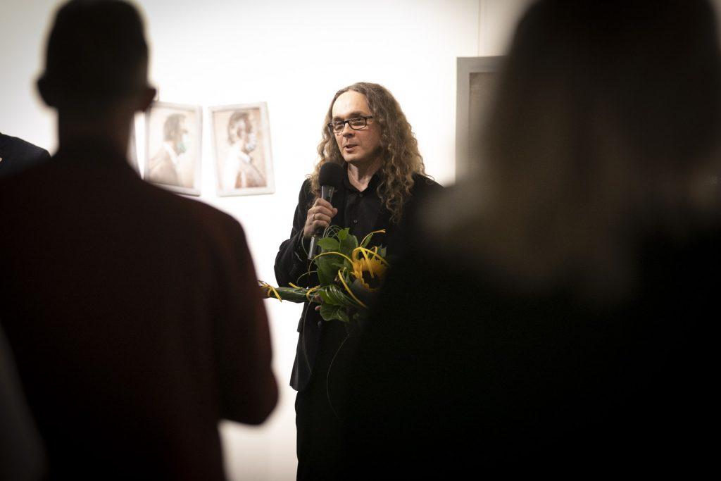Sala Wystawowa. Na ścianie wiszą fotografie. Mężczyzna ubrany na czarno trzyma w ręku mikrofon i bukiet kwiatów. Naprzeciwko niego stoi kilka osób.