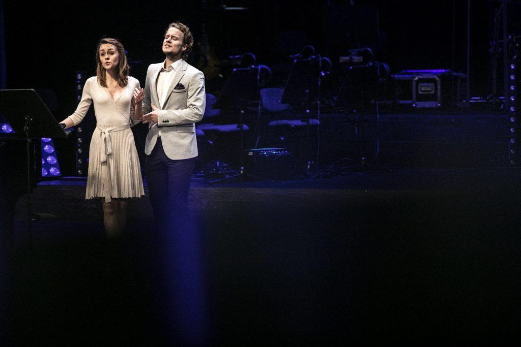 Kobieta i mężczyzna stoją blisko siebie. Przed nimi stoi pulpit do nut.