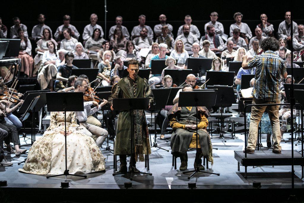 Na scenie trwa próba do koncertu. Z przodu siedzą soliści, jeden z nich stoi przed pulpitem śpiewając. Po prawej stronie, na podeście stoi dyrygent. Dalej gra sekcja smyczkowa Orkiestry Opery i Filharmonii Podlaskiej. Z tyłu w kilku rzędach siedzi chór.