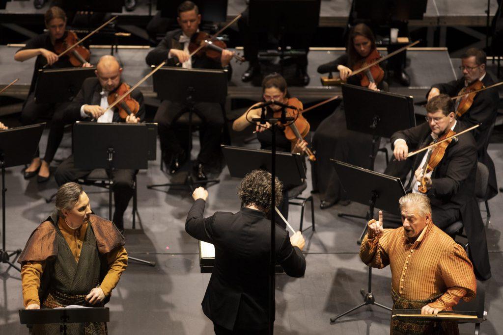 Dwóch solistów ubranych w stroje szlacheckie stoi przy dyrygencie. Dalej widoczna część grupy smyczkowej orkiestry
