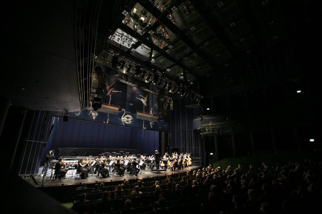 W oddali scena. Na scenie siedzi Orkiestra Opery i Filharmonii Podlaskiej. Bliżej widownia wypełniona publicznością co drugie miejsce.