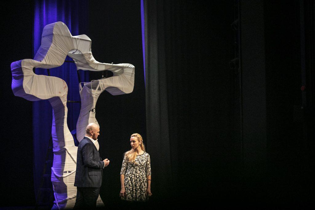 Na scenie kobieta i mężczyzna. Patrzą na siebie. Za nimi biały, duży krzyż.