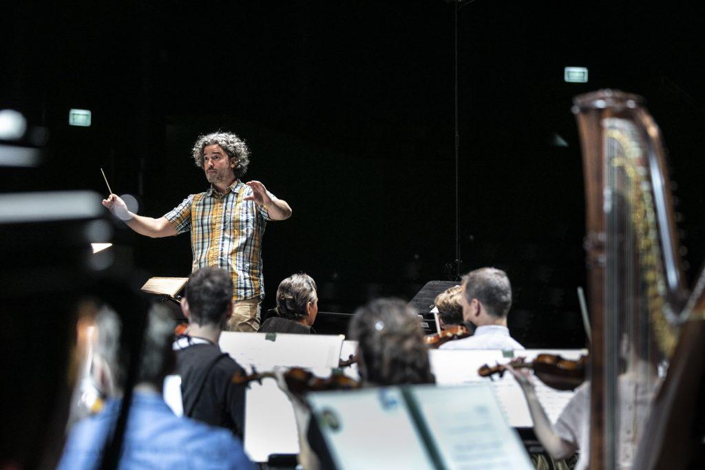 Z przodu, tyłem siedzi kilku muzyków z rozłożonymi nutami. Dalej, z podniesionymi rękami stoi dyrygent.