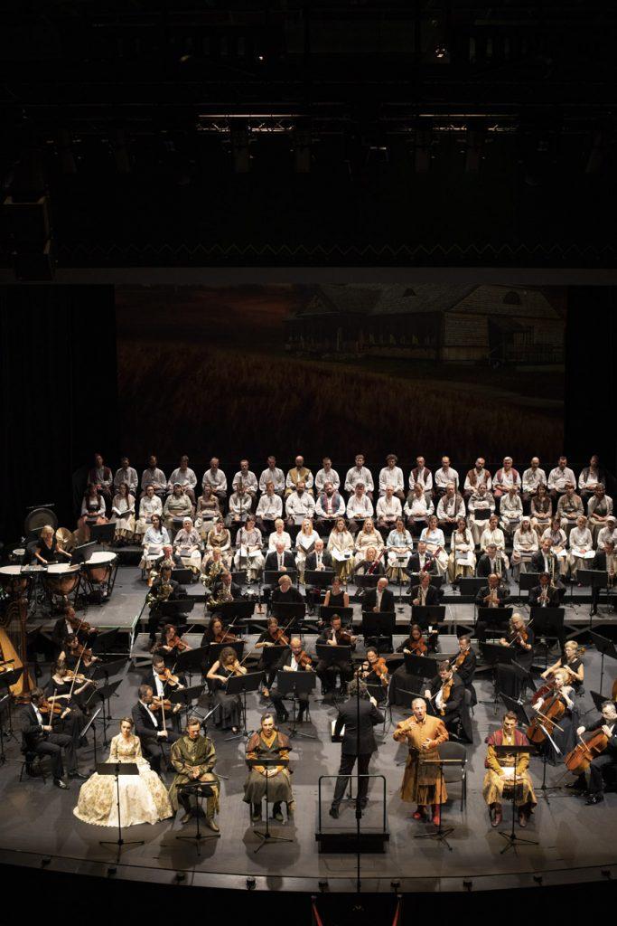 Widok sceny z góry. Z przodu siedzą soliści w kostiumach. Pomiędzy nimi stoi dyrygent. Za nimi siedzi orkiestra. Na końcu sceny, w kilku rzędach siedzi chór mieszany w białych kostiumach.