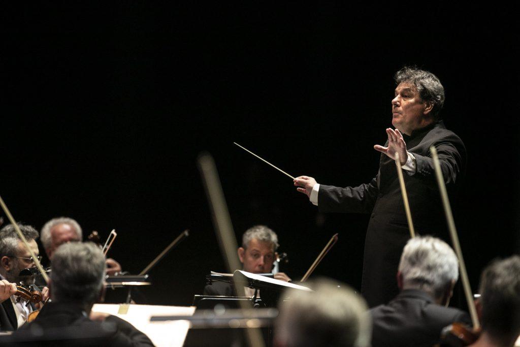Na środku, z uniesionymi rękoma stoi dyrygent. W ręku trzyma batutę. Przed nim kilku muzyków z grupy smyczkowej orkiestry.