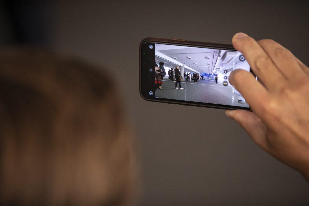 W kadrze telefon, na jego ekranie sala Wystawowa w której stoi kilkanaście osób.