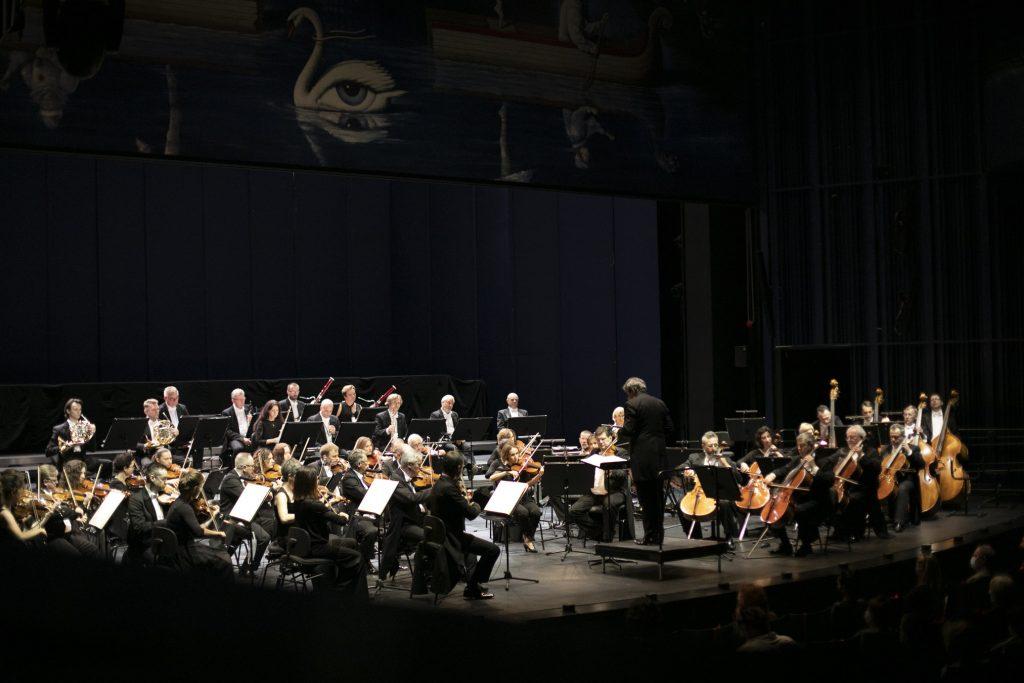 Na scenie Orkiestra Opery i Filharmonii Podlaskiej podczas koncertu. Na środku, na podeście stoi dyrygent.