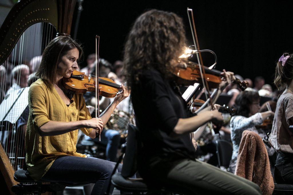 Na scenie siedzi Orkiestra Opery i Filharmonii Podlaskiej. Widok z boku. Na środku, na pierwszym planie dwie kobiety grające na skrzypcach. Po lewej stronie z przodu stoi harfa.
