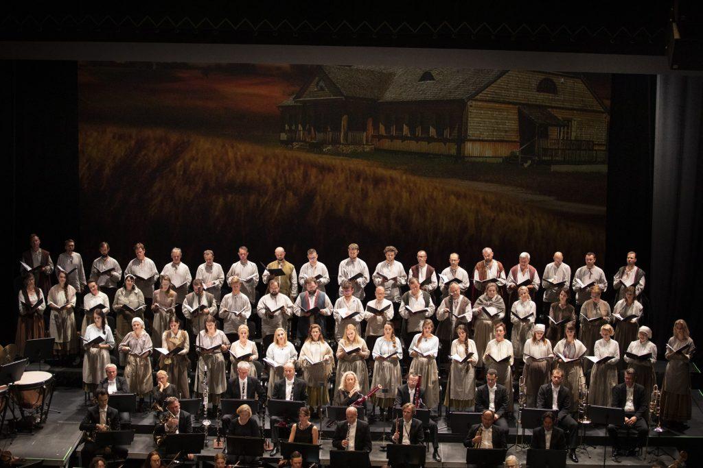 Zbliżenie na scenę. Z przodu siedzi grupa dęta orkiestry. Za nimi stoi w kilku rzędach chór mieszany. W tle scenografia przedstawiająca dwór szlachecki.