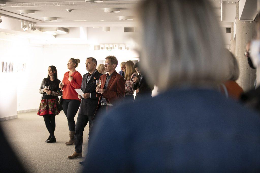 W sali wystawowej stoi kilkanaście osób, kobiet i mężczyzn. Wszyscy zwróceni są w jednym kierunku. Część osób trzyma kieliszki w dłoniach.