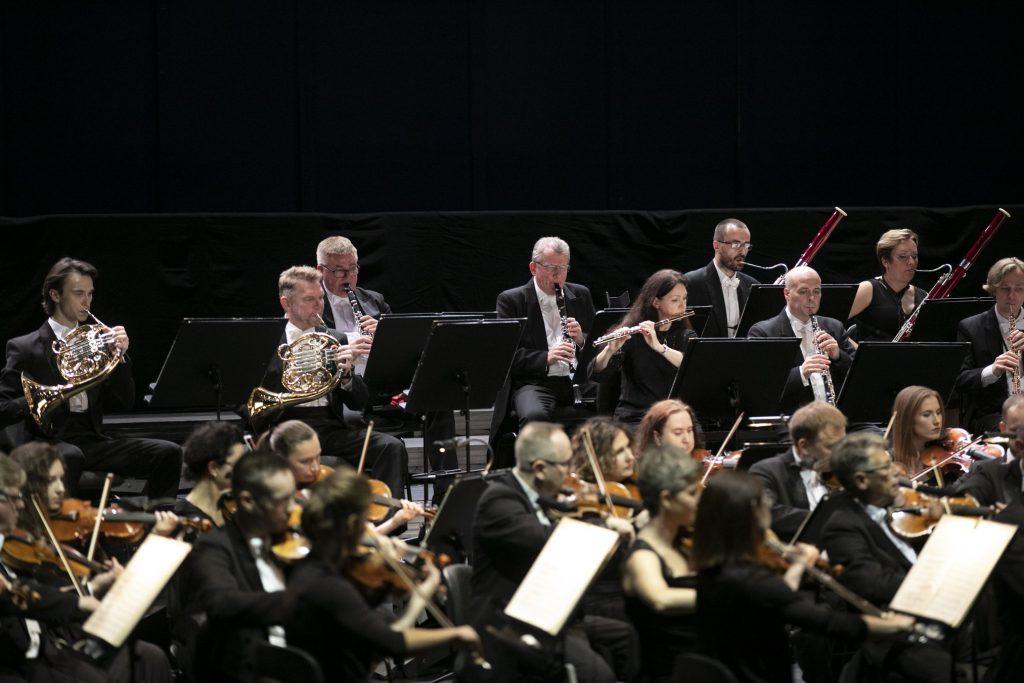Zbliżenie na część orkiestry Opery i Filharmonii Podlaskiej. Z przodu grupa skrzypiec, za nimi grupa dęta.