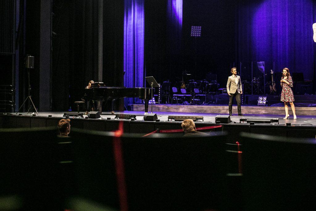 Na scenie w pewnej odległości stoi para, kobieta i mężczyzna. Po lewej stronie stoi fortepian, przy którym siedzi kobieta. Na widowni siedzi dwóch mężczyzn.