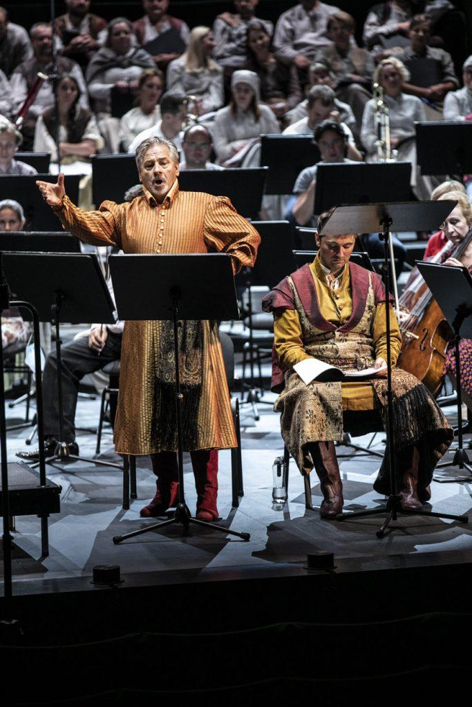 Na scenie, przy pulpicie stoi solista w stroju szlacheckim. Śpiewa trzymając rękę uniesioną do góry. Obok niego siedzi drugi solista. Patrzy w dół na rozłożony zeszyt. Za nimi część orkiestry i chóru.