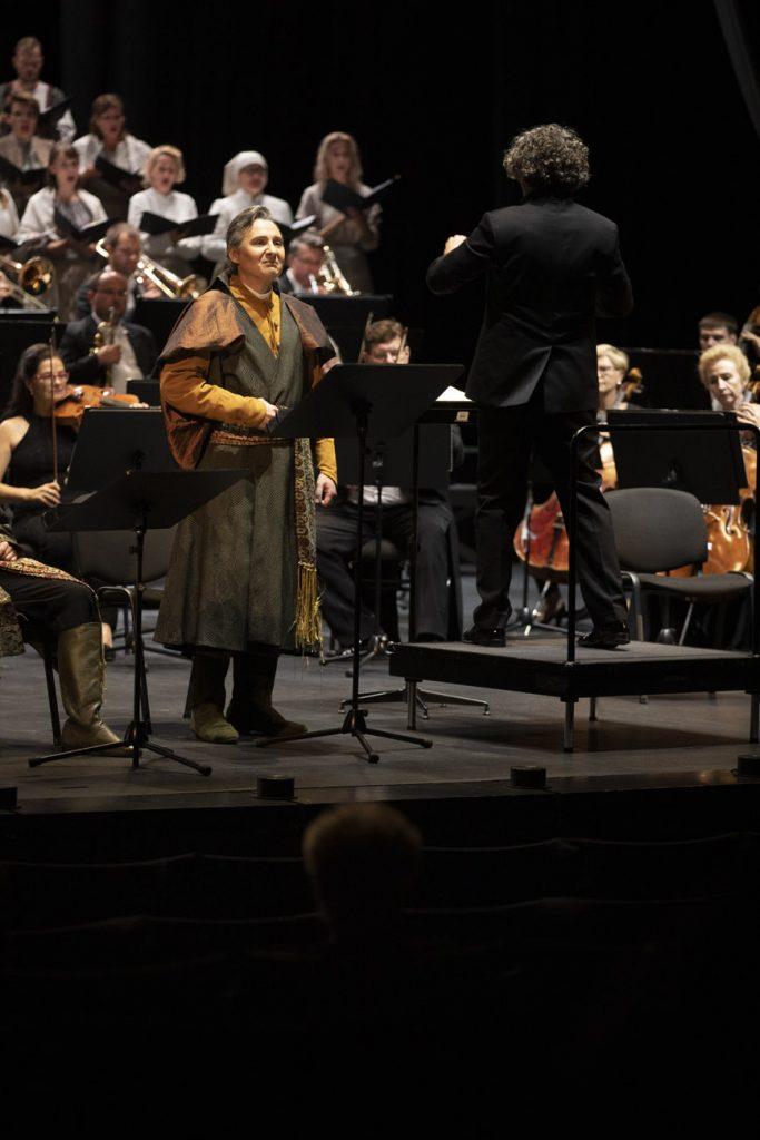 Na scenie po lewej stronie solista w stroju szlacheckim. Obok na podeście, stoi tyłem dyrygent. Dalej widoczna część orkiestry i chóru.
