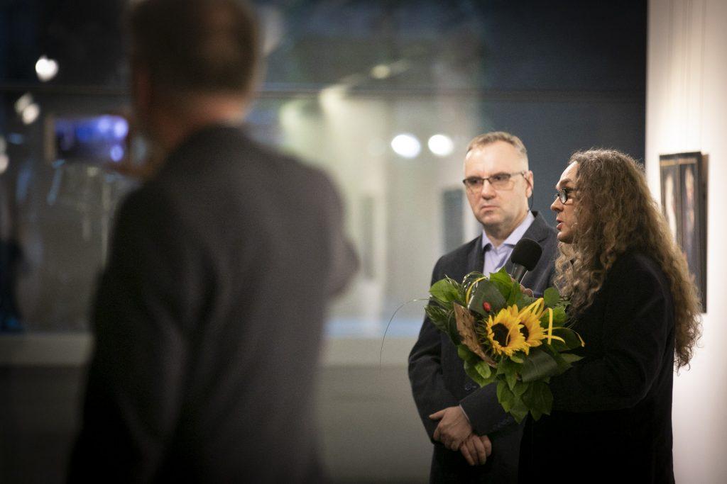 Po prawej stronie dwóch mężczyzn, jeden trzyma mikrofon i bukiet kwiatów. Po lewej stronie mężczyzna trzyma telefon robiąc zdjęcie.