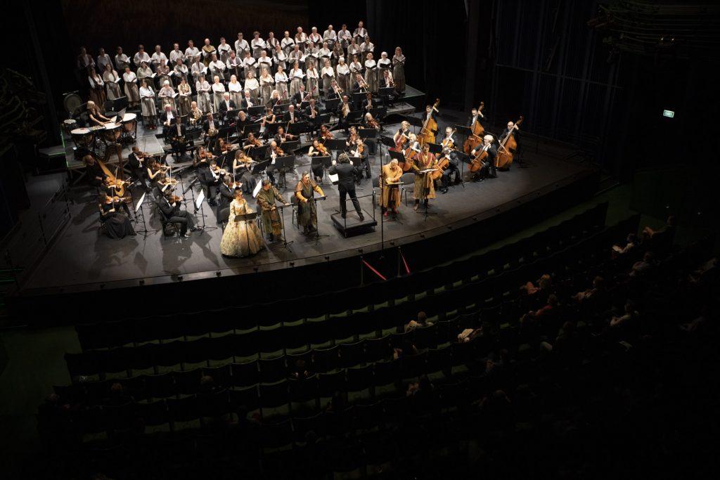 Widok sceny z góry. Z przodu, przy pulpitach stoją soliści w kostiumach. Pomiędzy nimi dyrygent. Przed nim siedzi orkiestra. Na końcu sceny stoi chór w białych kostiumach. Na widowni siedzi kilka osób.