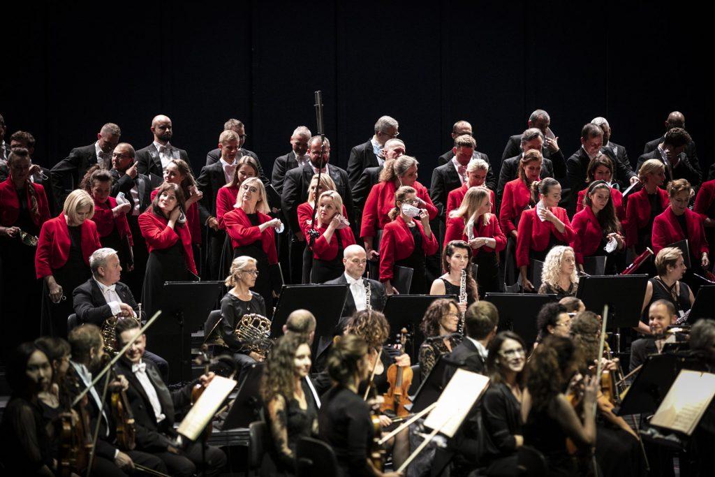 Zbliżenie na scenę. Na niej widoczna część Chóru, sekcja smyczkowa i dęta Orkiestry Opery i Filharmonii Podlaskiej przed koncertem. Część osób z chóru zdejmuje maseczki ochronne.