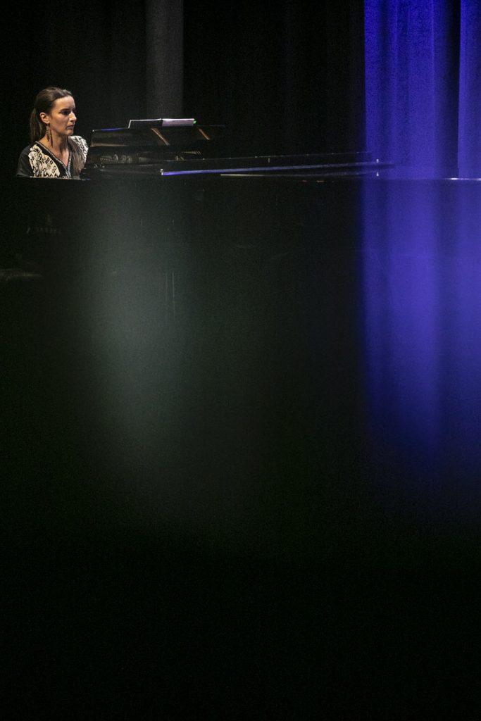 Zdjęcie przedstawia fortepian przy którym siedzi kobieta.