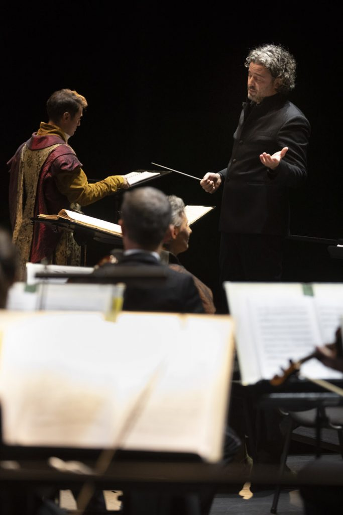 Po lewej solista w stroju szlacheckim odwrócony plecami. Po prawej dyrygent stoi przodem do orkiestry.