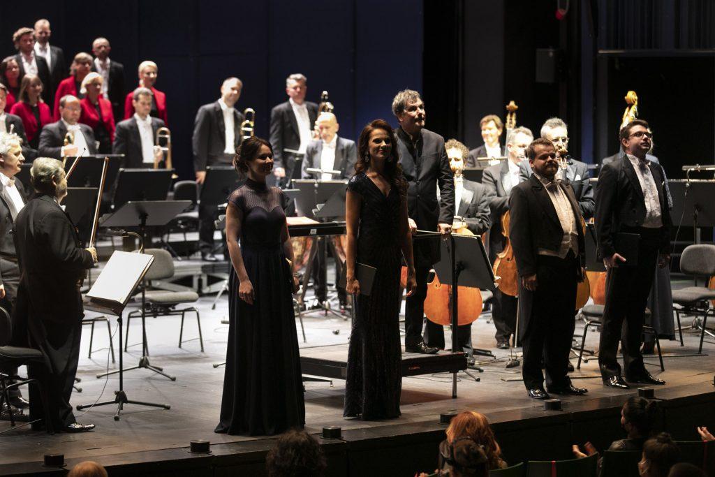 Na przodzie sceny stoi czwórka solistów, za nimi stoi dyrygent. Dalej po prawej stronie stoi grupa smyczkowa. Na końcu stoi część sekcji dętej. Za nimi widoczna część chóru.