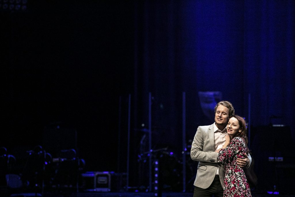 Scena oświetlona na niebiesko. Na niej kobieta z mężczyzną stoją przytuleni.