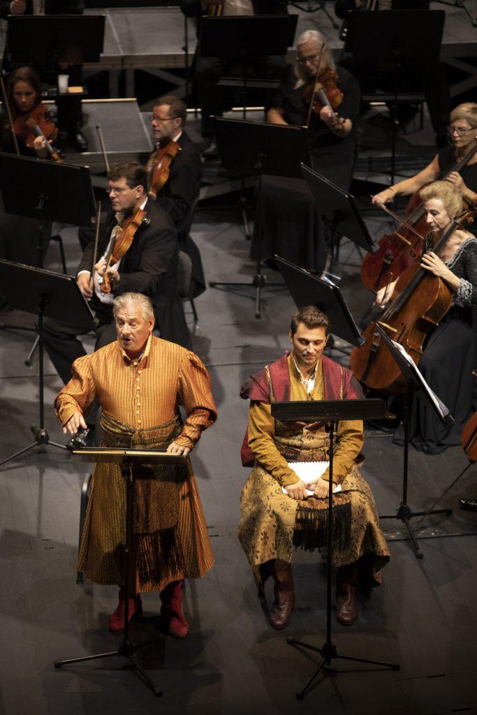 Z przodu dwóch solistów w kostiumach szlacheckich, za nimi część grupy smyczkowej orkiestry.