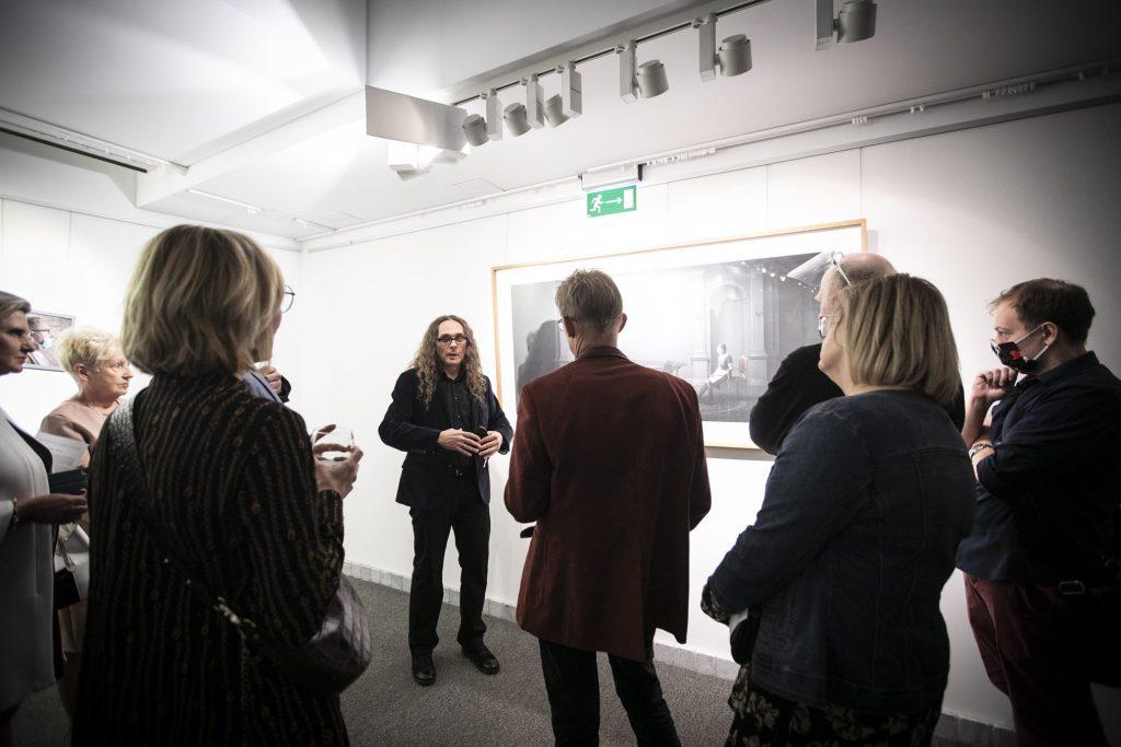 Grupa osób stoi przed obrazem wiszącym na ścianie. Mężczyzna w marynarce zwrócony jest do reszty osób. Trzyma ręce w geście tłumaczenia. Jedna z kobiet trzyma kieliszek w ręku.