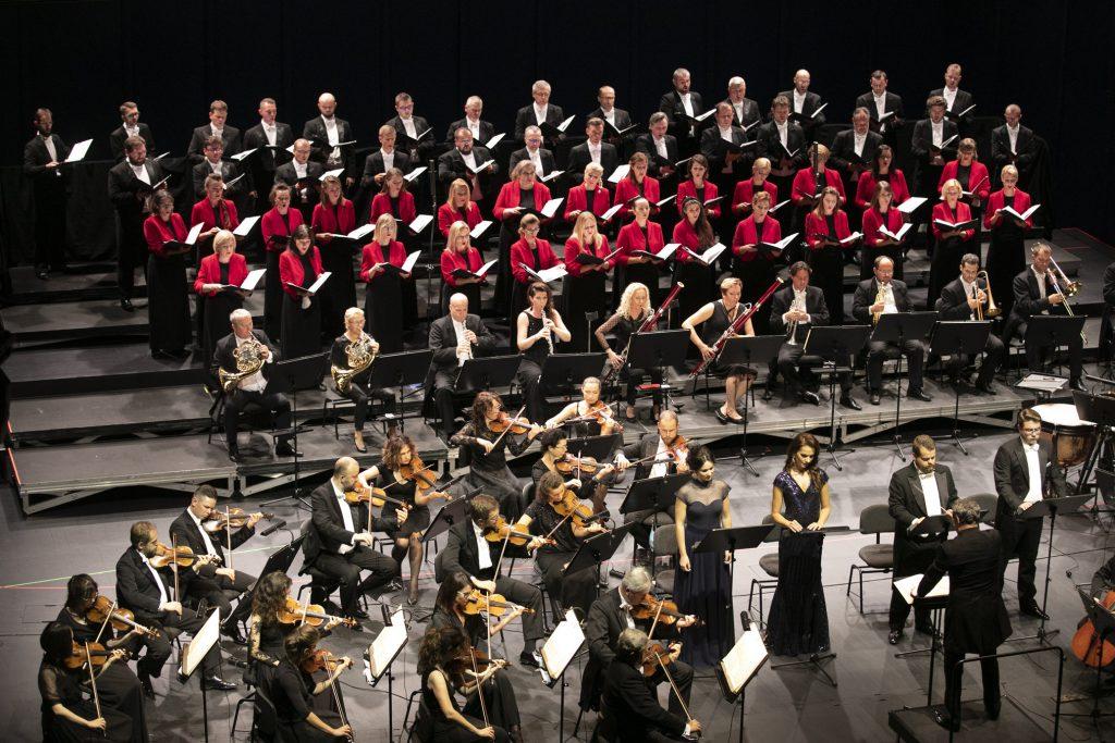 Na scenie stoją soliści, dwie kobiety w długich sukniach i dwóch mężczyzn we frakach. Po lewej stronie siedzi część grupy smyczkowej orkiestry. Dalej, w rzędzie siedzi sekcja dęta orkiestry. Za nimi, w kilku rzędach stoi chór mieszany. Wszyscy trzymają otwarte nuty.