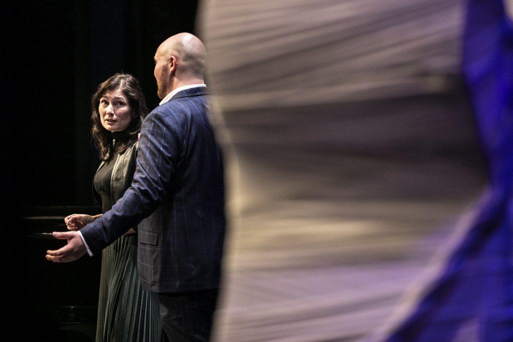 Dwie osoby na scenie. Kobieta patrzy na mężczyznę stojącego obok.