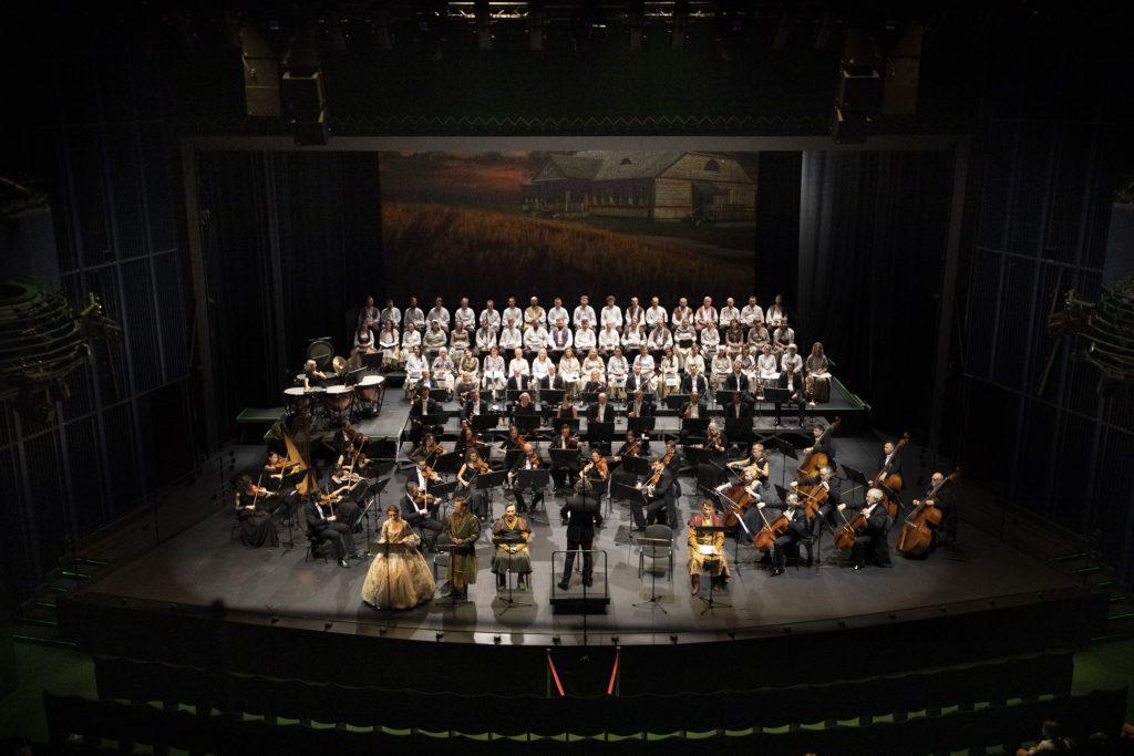 Widok sceny z góry. Z przodu siedzą soliści w kostiumach. Pomiędzy nimi dyrygent. Przed nim siedzi orkiestra. Na końcu sceny siedzi chór w białych kostiumach.