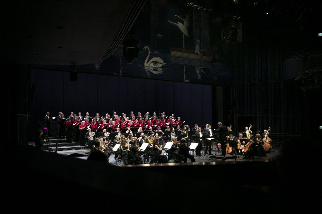 Zdjęcie zrobione z boku. Na scenie stoi czwórka solistów. Przed nimi dyrygent. Po obydwu stronach siedzi Orkiestra Opery i Filharmonii Podlaskiej. Za nimi, w kilku rzędach stoi chór mieszany.
