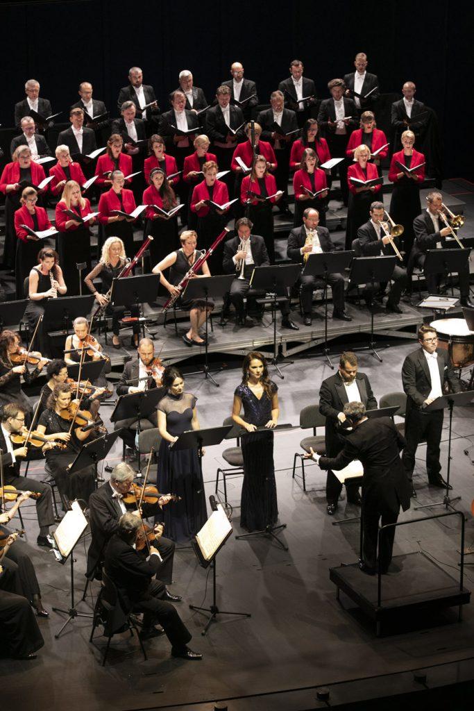 Zdjęcie zrobione z góry. Na środku stoi czterech solistów, dwie kobiety w długich sukniach i dwóch mężczyzn we frakach. Przed nimi stoi dyrygent. Po lewej stronie widoczna część grupy smyczkowej. Dalej siedzi w rzędzie grupa dęta. Za nimi, w kilku rzędach stoi chór mieszany.
