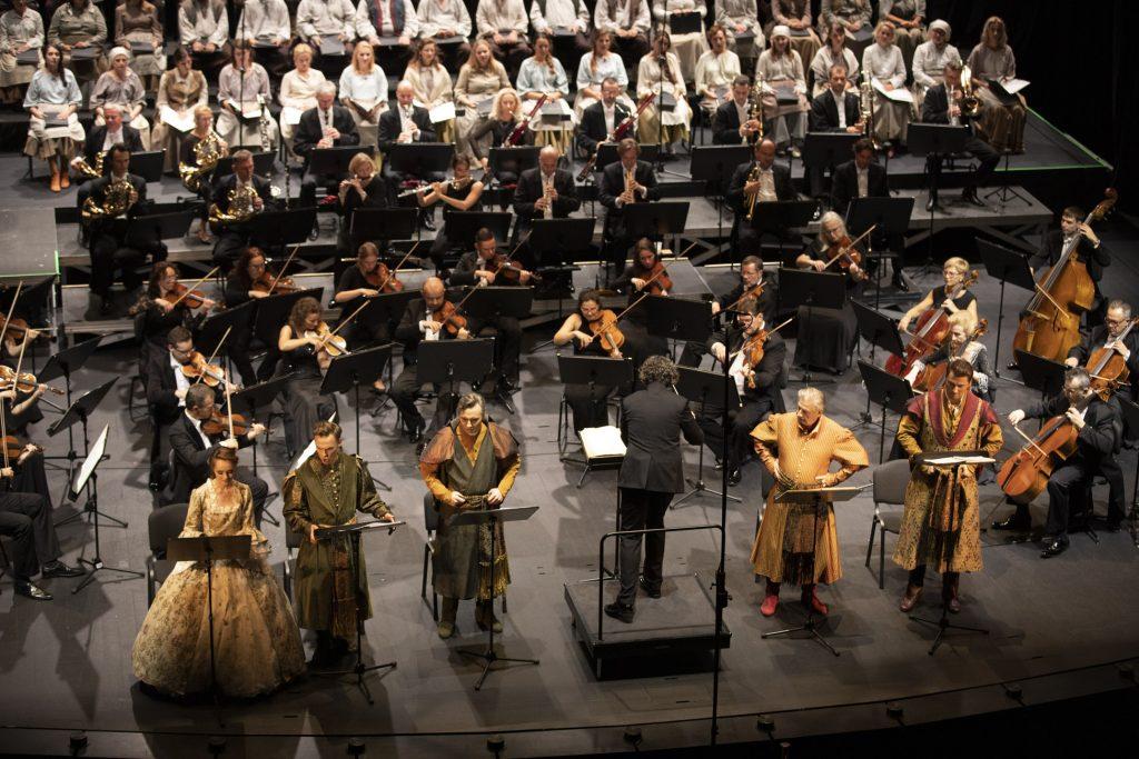 Z przodu stoją soliści w kostiumach i dyrygent. Za nimi siedzi orkiestra. Na końcu sceny siedzi chór w białych kostiumach.