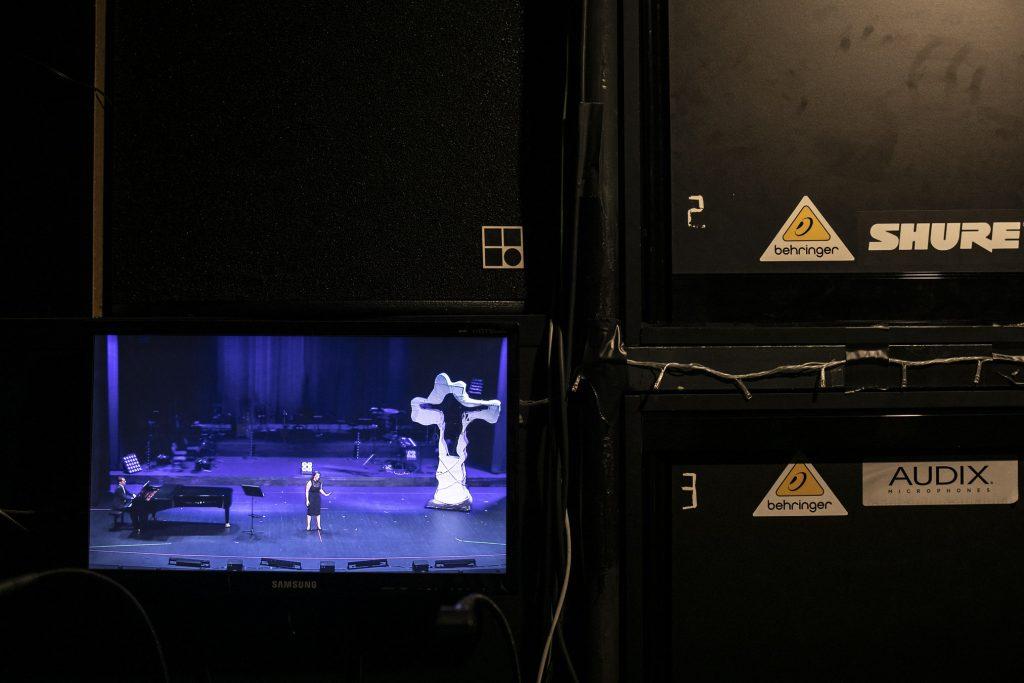Na czarnej ścianie wisi monitor. Na nim , na środku sceny , stoi kobieta. Po lewej stronie fortepian przy którym siedzi mężczzyna w garniturze.